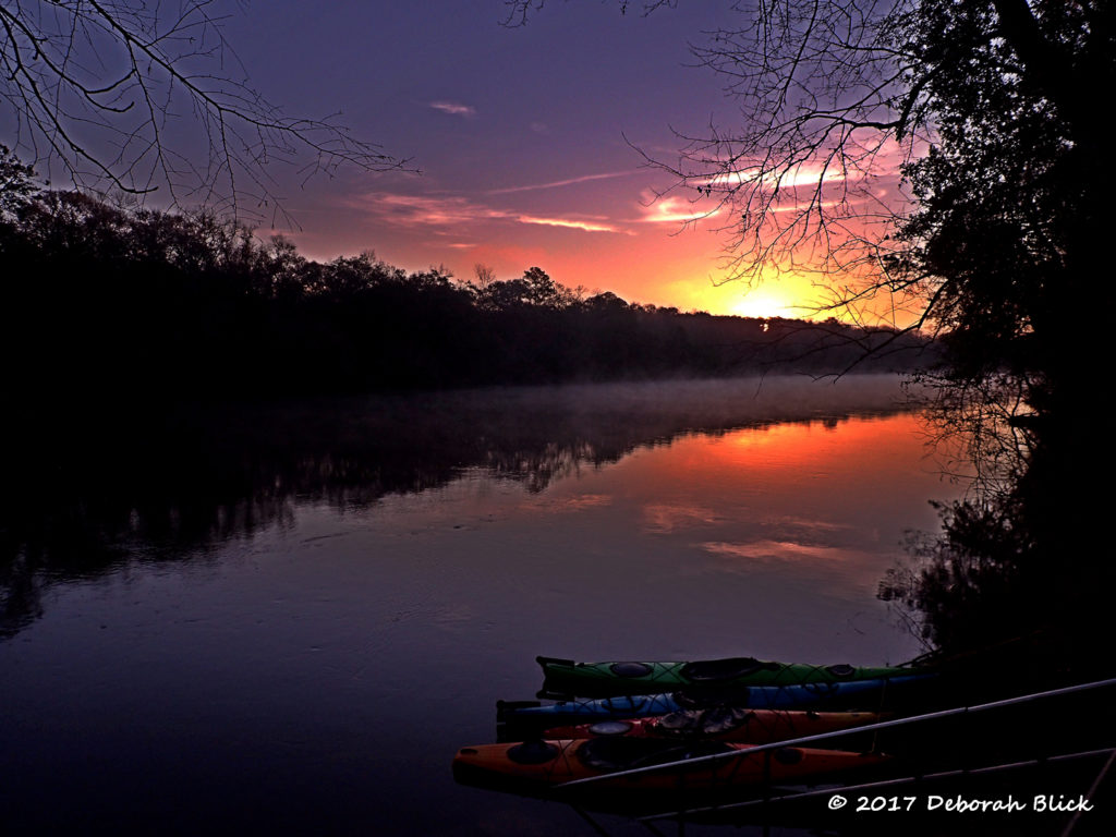 Sunrise over our kayaks at Adams Tract River Camp